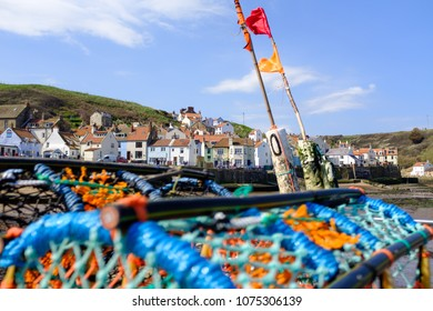 STAITHES, ENGLAND - APRIL 21: Staithes seafront with lobster traps in the foreground. In Staithes, England. On 21st April 2018.