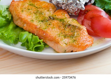 Stake from a salmon with vegetables on a plate. Closeup.