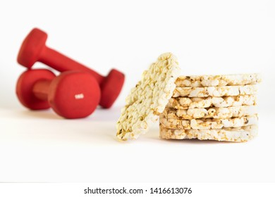 Staked crunchy rice cakes and unfocused red dumbbells on background. Helthy lifestyle sports concept.