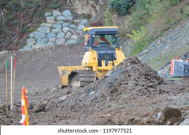 Stakes or markers provide visual elevations that a worker, using a small bulldozer, can reference as he clears and moves topsoil for a residential construction site.