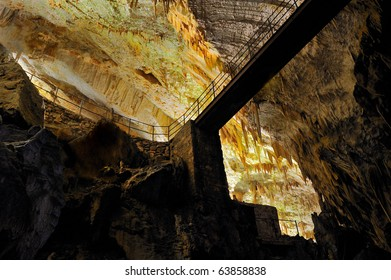 Stalactites, stalagmites and bridge in an underground cavern - Postojna cave