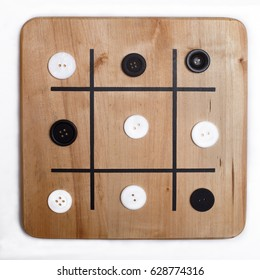 Stalemate at a game of tic-tac-toe with miscellaneous black and white buttons on wooden board