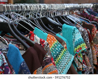 stall with many vintage clothes hanging for sale