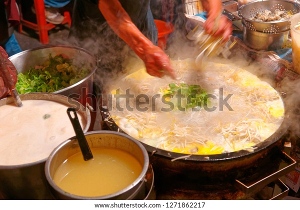 A stall vendor cooking Taiwanese oyster omelet, one of local people's favorite street-foods, with abundant ingredients in a steaming hot pan at his food stand, in Flower Night Market, Tainan, Taiwan