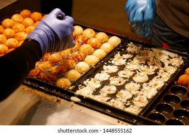 A stall vendor preparing Takoyaki, a ball-shaped Japanese savory snack made of flour-based batter filled with diced octopus & cooked in a molded pan & a popular street food in night markets in Taiwan