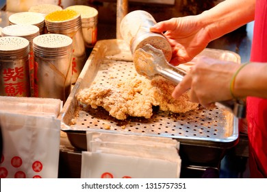 A stall vendor seasoning crispy deep-fried chicken cutlets with spice & salt, one of local people's favorite street-foods, in Raohe Street Night Market, Taipei, where traditional snacks can be savored