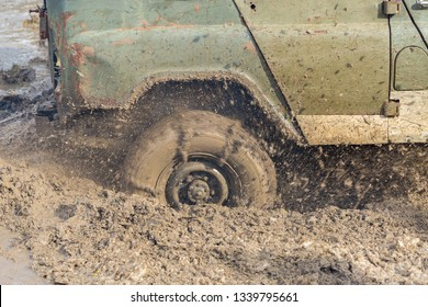 A stalled SUV rips out dirt and water from under the wheels. Close-up all-terrain vehicle.