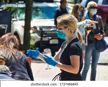 Stamford, Connecticut / USA - May 20, 2020: Waitress returns to duty in facemark and gloves as partial reopening took place. Stamford's Bedford St. shows life again.
