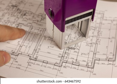 Stamp with finger on plan of house background. Finance and growth of business