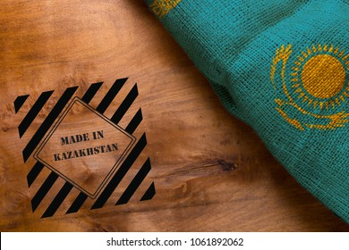Stamp made in Kazakhstan and Flag of Kazakhstan from rough fabric on a wooden background.