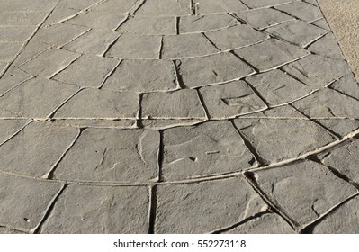 Stamped concrete pavement outdoor an expansion joint in the middle, mimics cobblestones circular waves pattern, cement patio design, decorative appearance of paving cobble stone, perspective