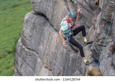 Stanage Edge,Derbyshire/Uk-08.01.2018:Active seniors.Mature woman-rock climber descending down the cliff attached to safety rope.Blurred landscape in background.