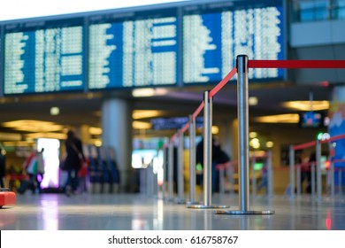 Stanchion barriers for waining lines in front of check in desks and flight schedule screens in airport on blurry background