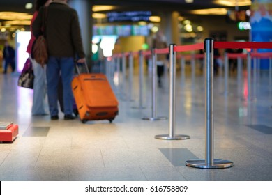 Stanchion barriers for waining lines in front of check in desks in airport on blurry background with passengers