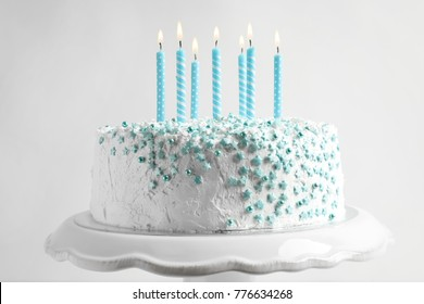 Stand with birthday cake and candles on light background