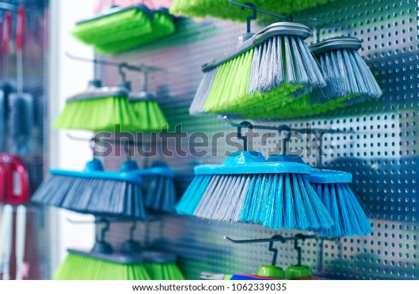 Stand with brushes for sweeping the floors in the store