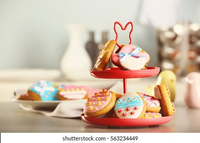 Stand with colourful Easter cookies on kitchen table