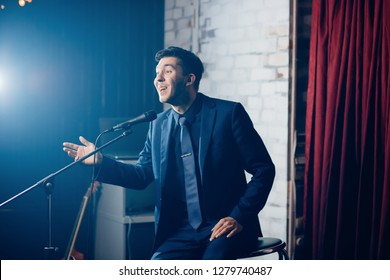 Stand up comedian on stage. Young man talks joke into microphone or sings songs.