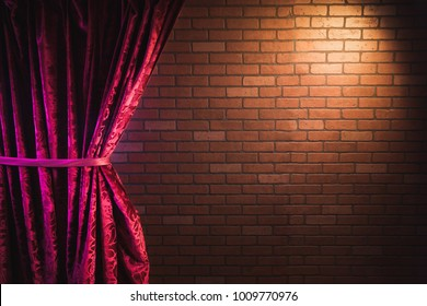 Stand up comedy background, red curtain and a brick wall with a reflector spotlight, high contrast image