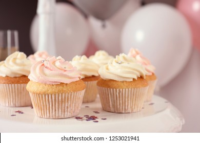 Stand with cupcakes and blurred balloons on background, closeup
