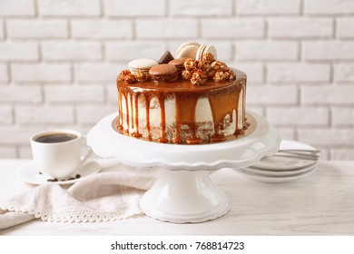 Stand with delicious caramel cake on table against brick wall