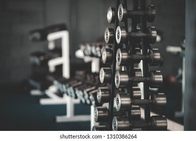 Stand with dumbbells in the gym, dumbbell set. Many dumbbells in the fitness club