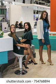 Stand girls are standing at the counter. St. Petersburg, Russia - 3 October, 2017. Young girls and women at the St. Petersburg gas forum.