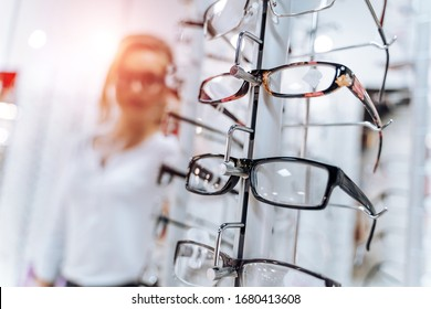 Stand with glasses in the store of optics. Woman chooses glasses.