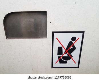 'Don't stand on the toilet seat' sign inside a dirty public toilet