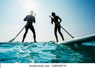Stand up paddle board couple paddleboarding .Selective focus. People blured with water spray.