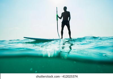 Stand up paddle board man paddleboarding . Young caucasian male model on Thailand beach on summer holidays vacation travel.