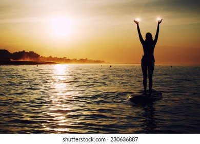 Stand up paddle board yoga performed by beautiful woman with bright sunset on background, yoga training in harmony with nature, silhouette of yoga woman holding lights in the hands, spiritual concept