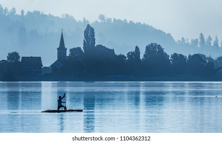 Stand up paddle boarder near the village of Busskirch (Kirchdorf), Rapperswil-Jona, Sankt Gallen, Switzerland. Located in an idyllic lakeside shore of the Obersee (Upper Lake Zurich)
