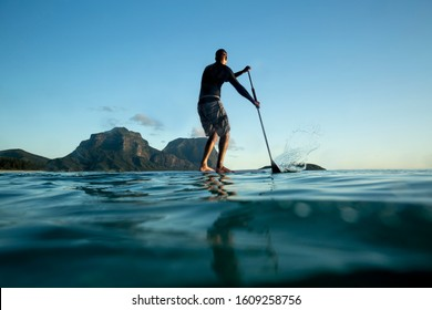 Stand Up paddle boarding on Calm ocean water, young adult surfer male standing on a surfboard and using a paddle, water surface rear view, Mount Gower and Mount Lidgbird view, Lord Howe Island