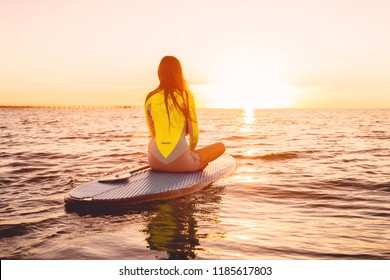Stand up paddle boarding on a quiet sea with sunset colors. Relax in ocean