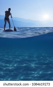Stand up paddle boarding. Young man floating on a SUP board. Underwater view of sea, copy space for text
