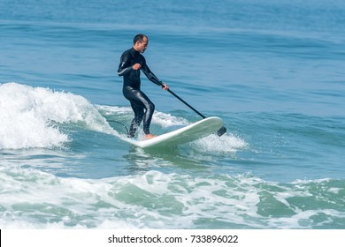 Stand up paddle surfer catching a wave on the atlantic ocean.