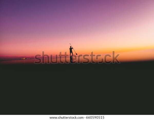 Stand up paddle surfing in ocean with beautiful colorful sunset or sunrise colors