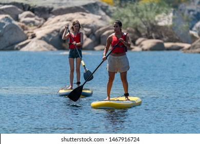 Stand up paddleboarding on lake. Watersport on lake. Tourist outdoor activity at Lagoa Comprida, Serra da Estrela National Park in Portugal.