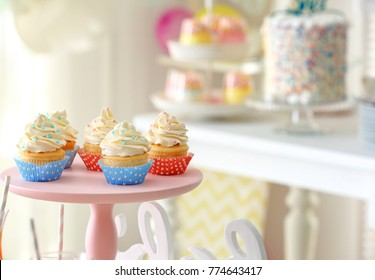 Stand with tasty cupcakes indoors, closeup