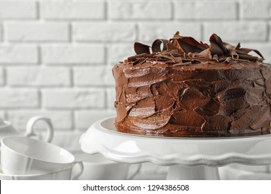 Stand with tasty homemade chocolate cake near white brick wall