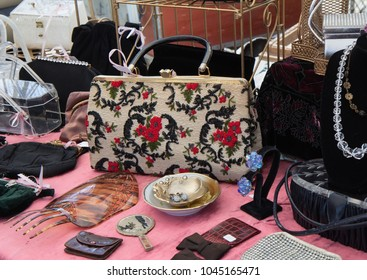 Stand with vintage embroidered purse, costume jewelry and more at flea market