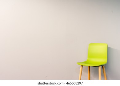 Standalone chair in modern design placed in front of the gradient grey wall for interior or graphic backgrounds. The picture can be used as a metaphor to represent the hiring position.