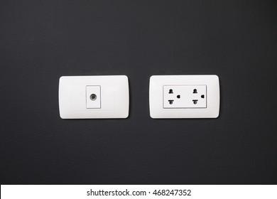 standard asia wall socket on a black concrete wall