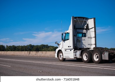 Standard big rig semi truck for local transportation of goods and commercial cargos with aerodynamic spoilers along perimeter of the day cabin to reduce air resistance and save fuel running on highway
