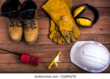 Standard construction safety equipment on wood background