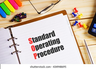 """Standard Operating Procedure"" text on paper in open diary with spectacles, colourful push pin, pen and calculator on the wooden table - business and finance concept"