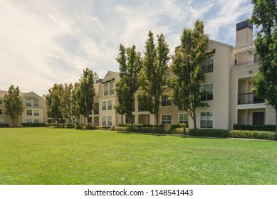 Standard view apartment building complex with grassy backyard in Palo Alto, California, USA. Summer cloud blue sky
