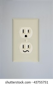 A standard wall electrical outlet contains two surprised faces. This one has one replaced by a confused face.
