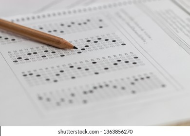 Standardized test exam multiple carbon paper form with gray black answers sheet bubbled and pencil resting on university classroom. Examination knowledge in school concept